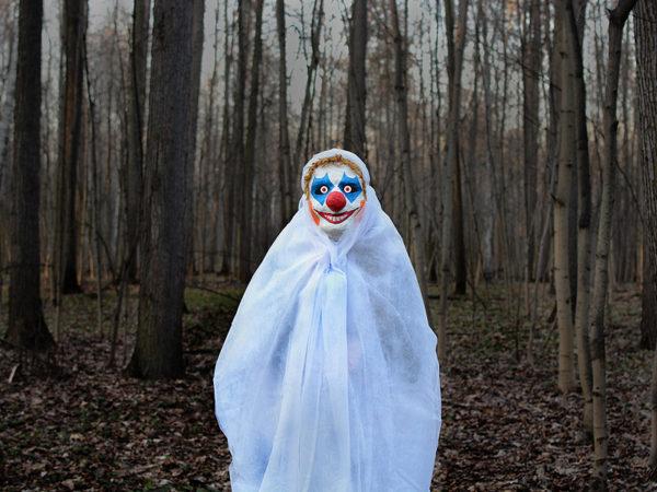 evil+clown+in+a+mask+standing+in+a+dark+forest+in+a+white+veil