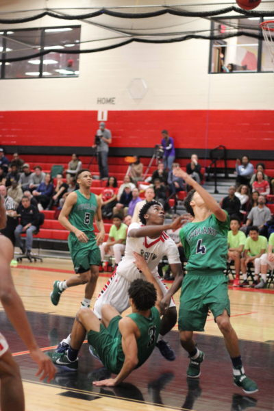 Feature+Photo+By%3A+Vanessa+Guereca-+Sophomore+Jodaun+Dotson+is+knocked+down+after+a+shot+as+the+Overland+Blazers+attempt+to+clock+his+shot.+The+Raiders+lost+71-65+in+the+final+minutes+to+Overland.