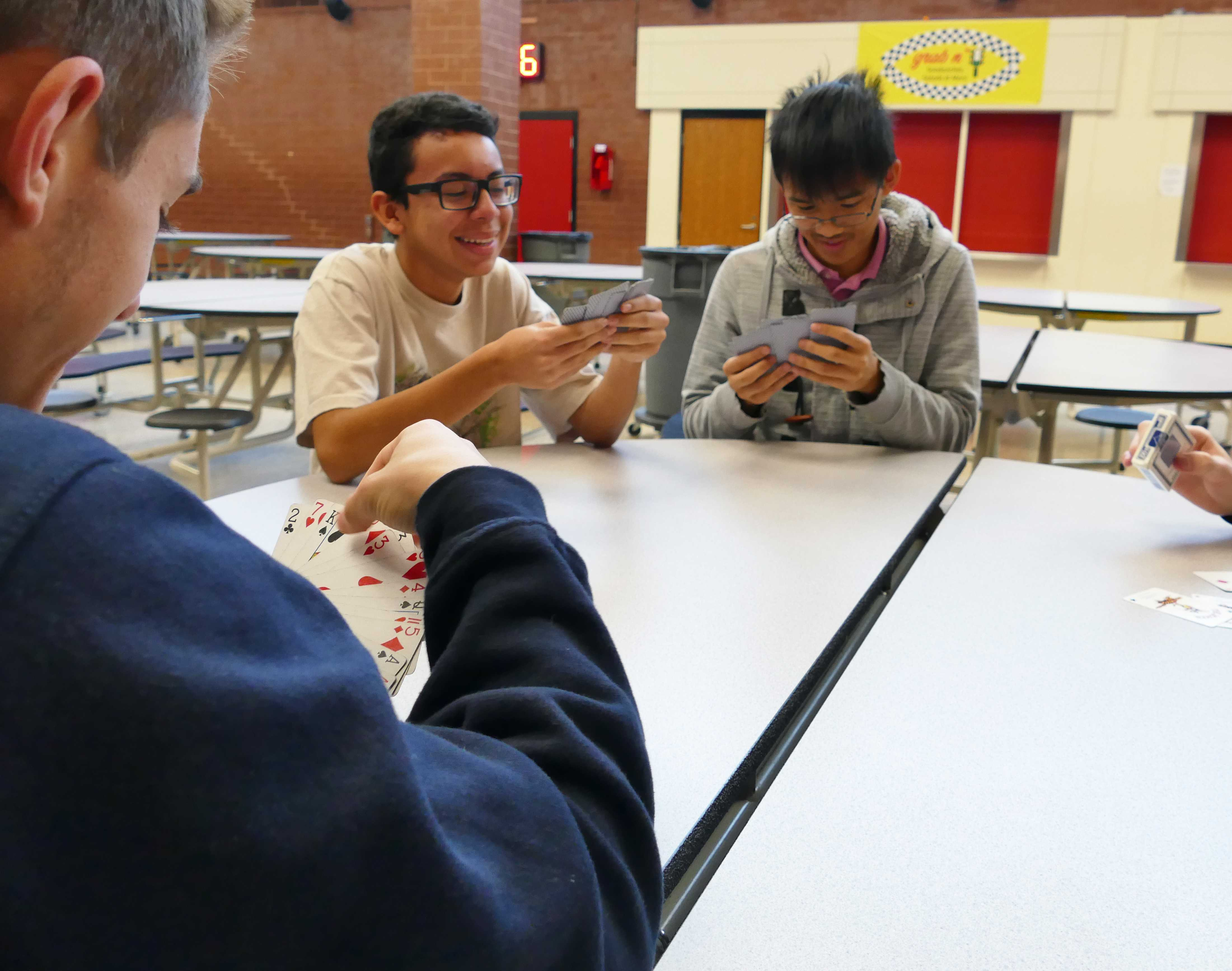Juniors Jordan Alvarenga (background left) and Kenny Luong (background right) play a card game with senior (foreground) in a moment of relaxation before Thanksgiving Break. Students will not have school from Wednesday, November 22 to Sunday, November 26.