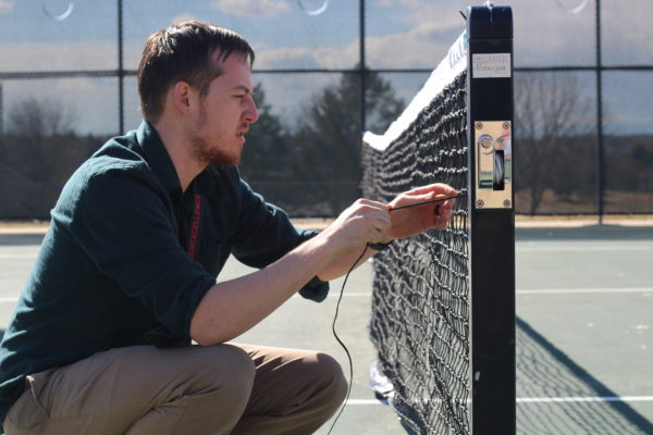 Feature+Photo+By%3A+Vanessa+Guereca+-+First+year+coach%2C+Mr.+Larson+finishes+up+setting+up+the+tennis+nets.+Spring+sports+are+in+full+swing+as+the+spring+season+has+arrived.+Every+year%2C+the+tennis+nets+and+courts+receive+damage+by+outside+students.+