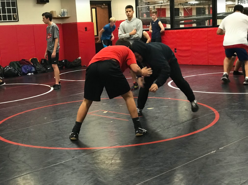 Wrestlers practicing takedowns as one of their beginning drills for the day. Observers looking out for tips on how to improve their movements.