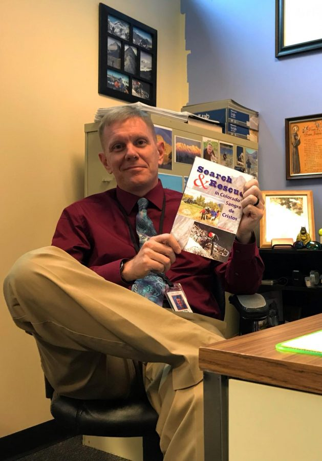 Mr.+Wright+poses+with+his+book+after+school.+Sometimes+during+class%2C+if+the+topic+is+relevant%2C+he+recommends+the+book+to+some+students+that+could+find+it+interesting.