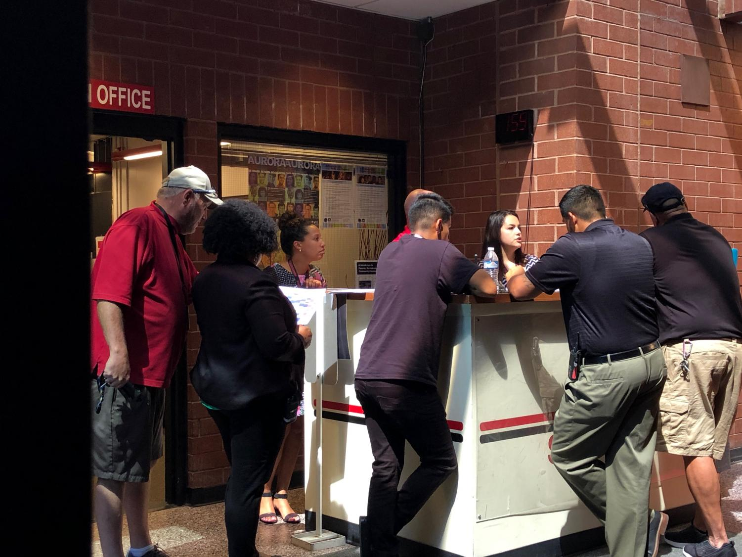 Some of the security administration meet at the front lobby desk discussing matters. Many watch the halls and rotate through checking different areas of the school at different times. (Stephanie Pickens)