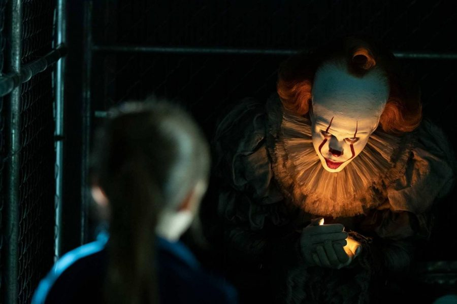 Pennywise+uses+a+lightning+bug+to+lure+a+little+girl+into+his+grasp.+%28Photo+by+Warner+Brothers%29