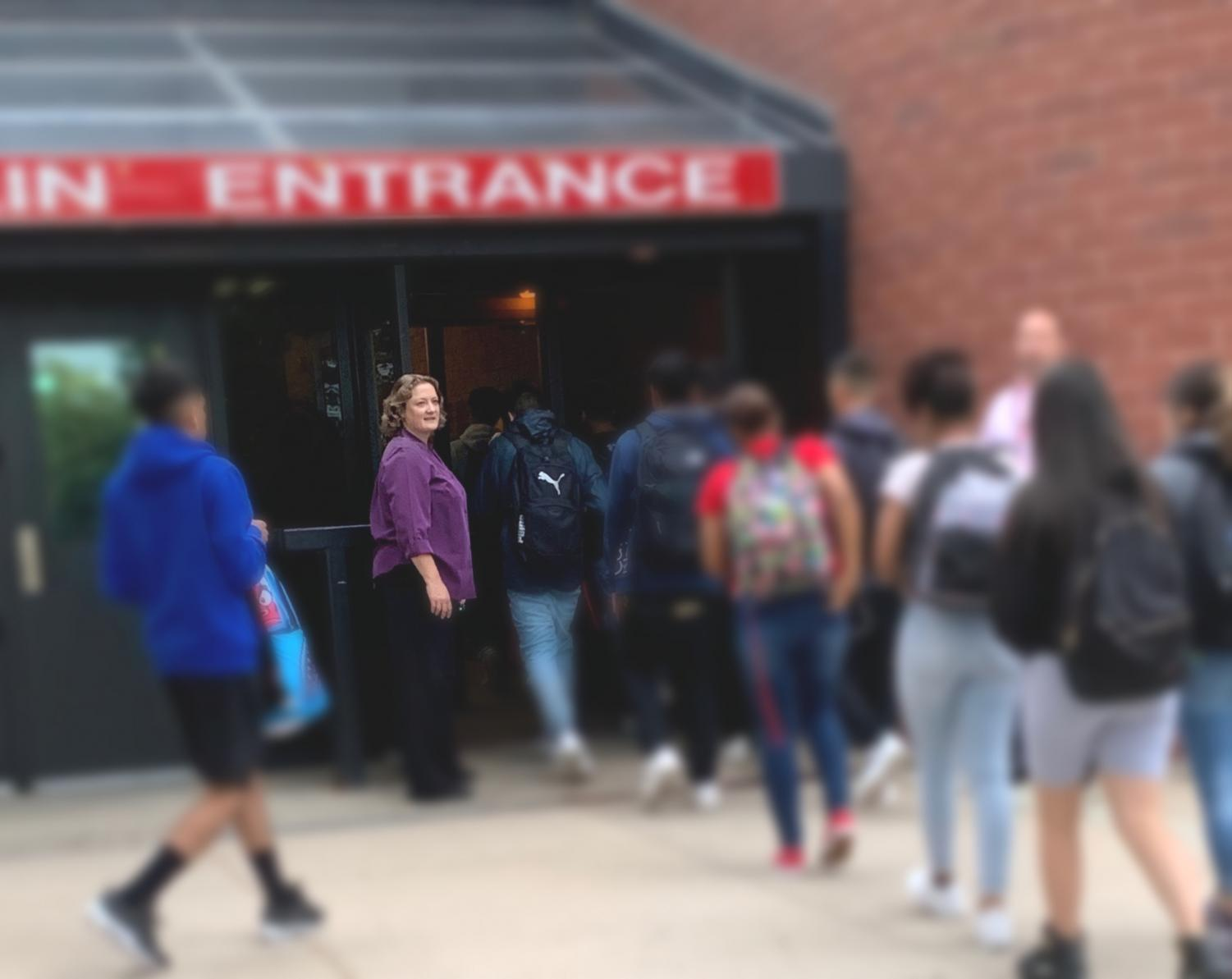 Lisa Grosz stands outside at the front doors before first period. She greets each student as they walk inside to begin their day. (Caroline Smith)