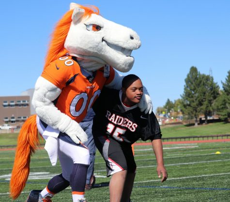 Micah Ross and Miles the mascot hold onto each other as they prepare to make a play.