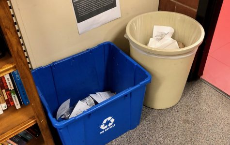 Feature Photo by Brianna Sanchez - A recycling bin and a trash can are placed side by side in an English classroom. The recycling bin contains paper and a water bottle, while the trash can also hold paper.