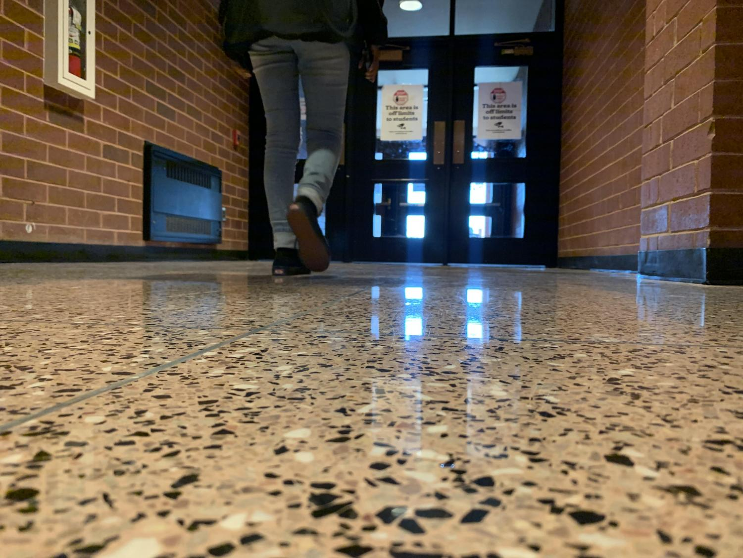 "Blessed Asare walks through the ""off limits"" door after the 3:21 bell rings. Students throughout the school use these doors to exit the building faster than leaving by the front entrance."