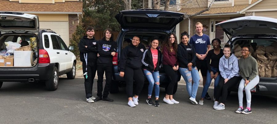 National Honor Society members pose in front of three cars filled with bags (Mary Steinkamp).