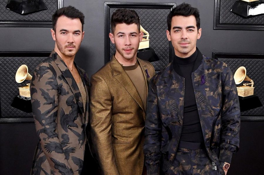 The+Jonas+Brothers+stand+together+and+pose+for+the+camera+while+on+the+red+carpet+at+The+Grammy+Awards.