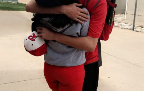 Feature Photo by: Melanie Aguirre - Two students hug each other after school before walking to practice.