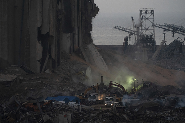 Trucks and workers sift through rubble shortly after the explosion in Lebanon in an effort to start searching and cleaning. (Infoplease)