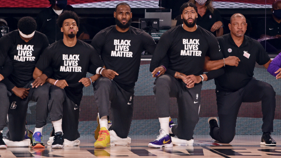 The+Lakers+and+Clippers+kneel+together+before+their+match-up+in+the+Orlando+Bubble.+Teams+are+wearing+Black+Lives+Matter+shirts+during+all+pre-game+activities.