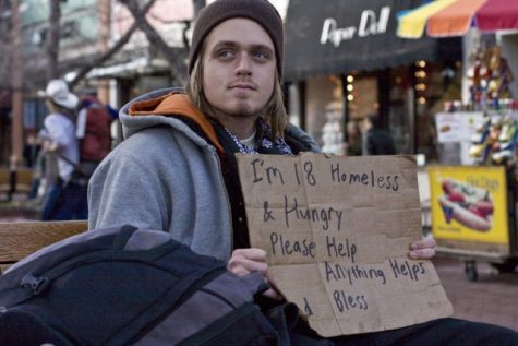 An 18 year old man stands outside some businesses downtown with a cardboard sign in hopes of receiving some donations. Feature Story: (Boulder Weekly)