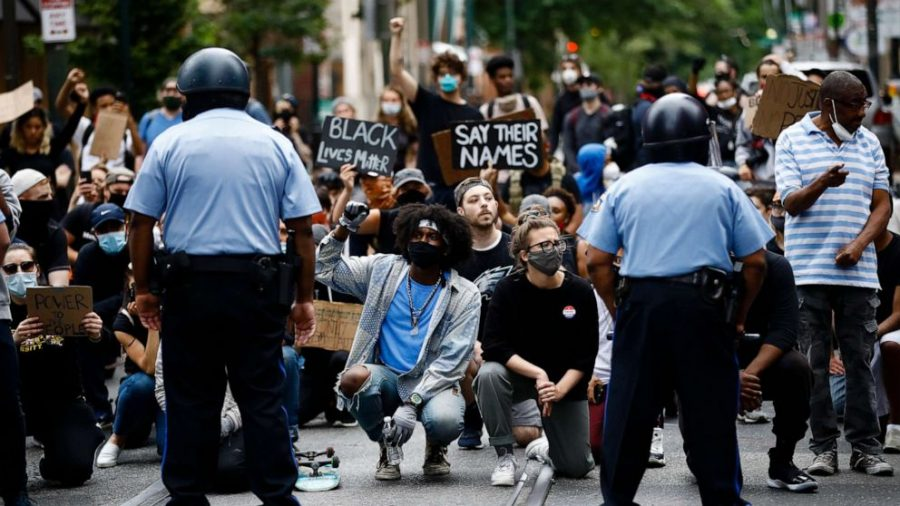 Black Lives Matter protesters are on their knees holding signs. The fist, a symbol of black power and resistance to injustice is held up by many of the protesters. (ABC News)