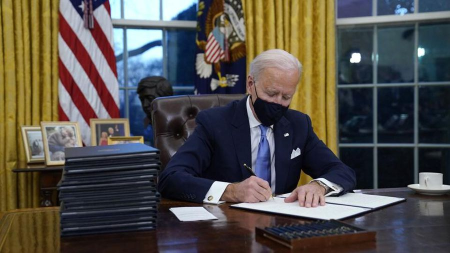 President Joe Biden sits in the Oval Office while signing several documents. (AP News)