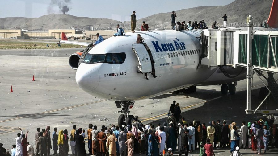 Citizens of Kabul loading onto a plane, with bystanders standing around watching the people. (Photo Credit - AFP)